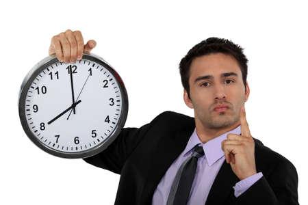 deadline: Stern businessman with a clock