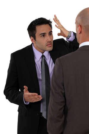 disagreeing: Two businessmen disagreeing