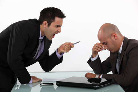 people arguing: Businessman screaming at a colleague