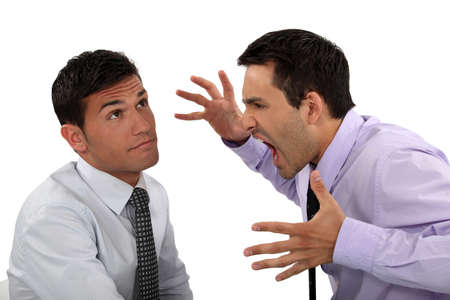 impervious: Businessman shouting at a colleague Stock Photo