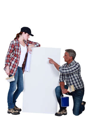 tradeswoman: Tradespeople looking at a blank sign