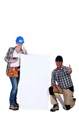 Thumbs up from carpenters with a blank board photo