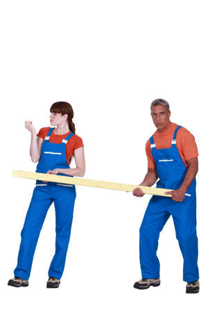 disinclination: Man and woman holding wood