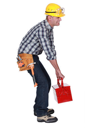 A construction worker with a heavy toolbox Stock Photo - 16842106