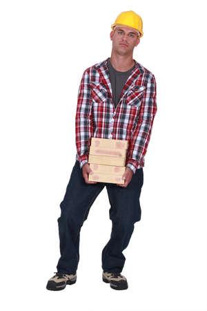 Man carrying pile of bricks Stock Photo - 16890051