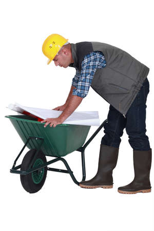 drawing safety: Tradesman looking at a blueprint while leaning over a wheelbarrow Stock Photo