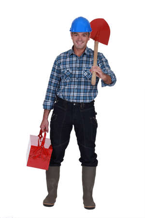 Tradesman carrying a spade and a toolbox photo