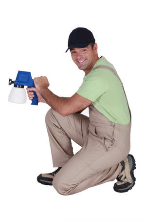Man kneeling with paint sprayer Stock Photo - 16842116