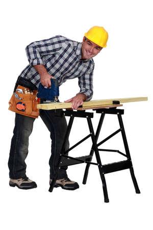 serrucho: Un hombre que usa una sierra de calar