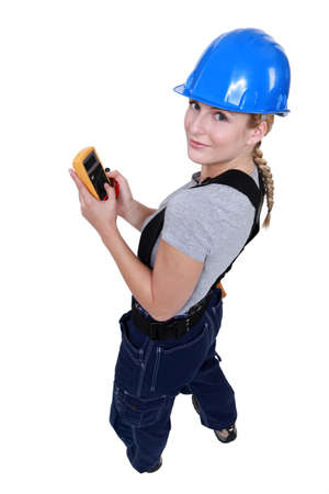 multimeter: Female electrician with a voltmeter