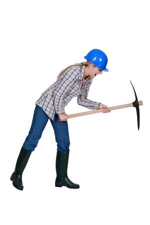 pickaxe: Tradeswoman using a pickaxe Stock Photo