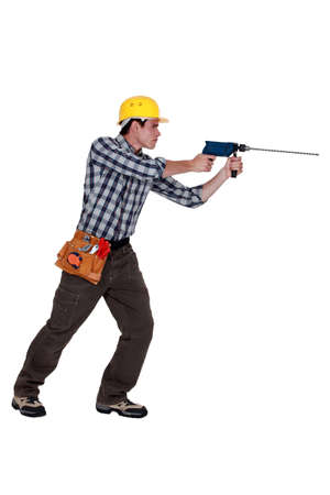 electric drill: Man using drill with long bit Stock Photo