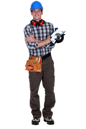 Portrait of a young tradesman holding a circular saw photo