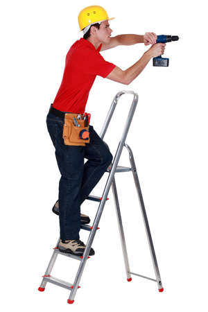 Determined tradesman using a power tool photo