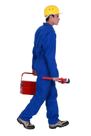 plumber walking with toolbox and spanner photo