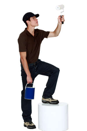 Young man holding a paint roller photo