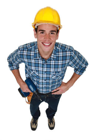 power operated: Young tradesman holding a power tool