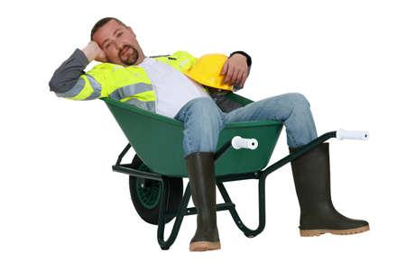 slumped: Lazy worker slumped in wheelbarrow