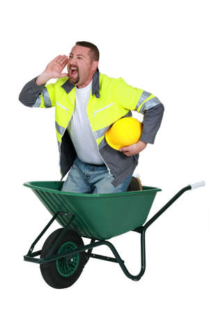 barrow: Mason shouting whilst stood in wheelbarrow Stock Photo