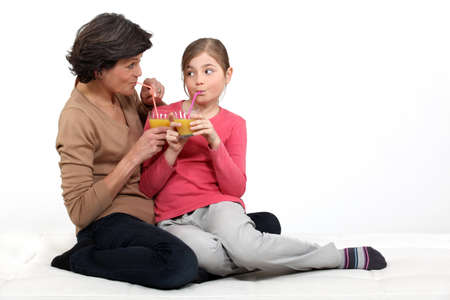 50s adult: Little girl having a drink with her grandma Stock Photo