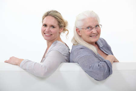 Mother and daughter sitting on white sofa photo