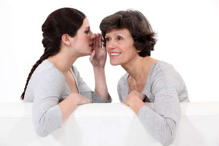 telling: Woman telling her mother a secret Stock Photo
