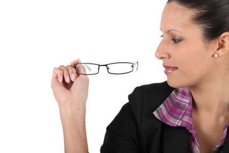 Woman looking at her eyeglasses photo