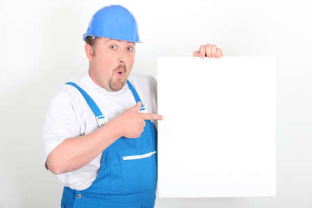 astonished: Surprised tradesman holding a blank sign Stock Photo