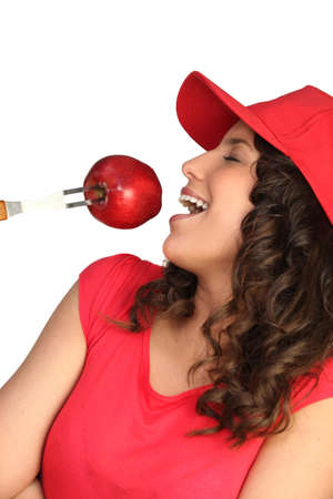 on cloud nine: Woman eating a red apple Stock Photo