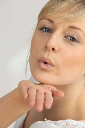 Blond girl blowing kisses photo