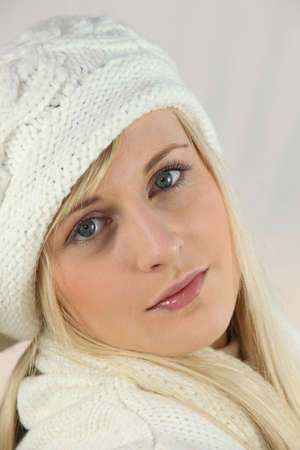 Young woman in a white knitted hat and scarf photo