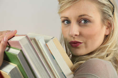 puckered lips: Woman carrying a stack of books Stock Photo