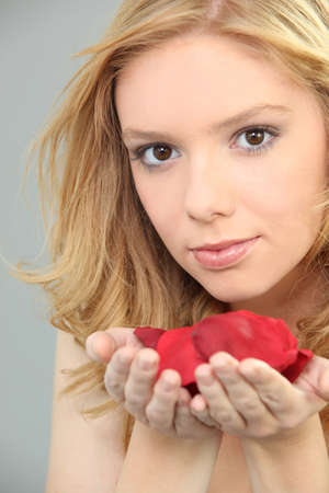 Young woman with a handful of rose petals Stock Photo - 16901539