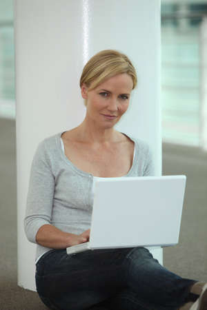 Woman sat next to column using laptop computer photo