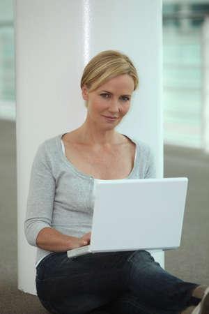 microcomputer: Woman sat next to column using laptop computer Stock Photo