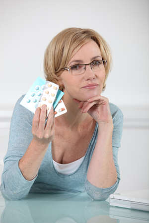 Blond woman holding various prescription drugs photo
