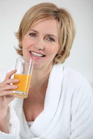 bath gown: Woman drinking orange juice
