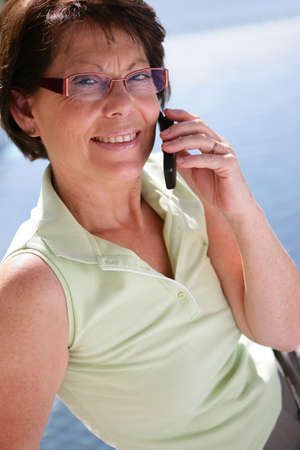 Middle-aged woman making call outdoors photo