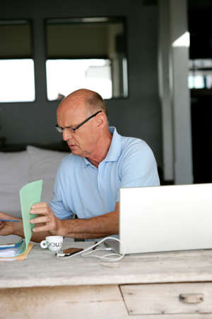 Senior man trying to sort hiss house bills out photo