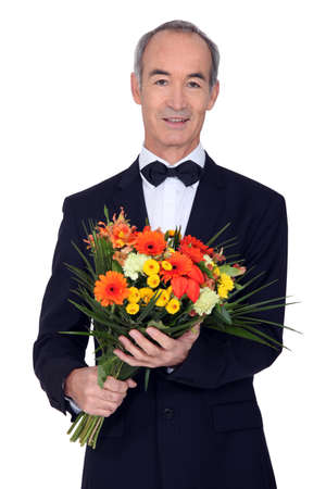 senior man in a suit holding flowers photo