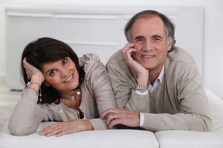 Middle-aged couple lying on a futon Stock Photo - 16901709
