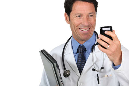 Doctor with a cellphone and laptop computer photo