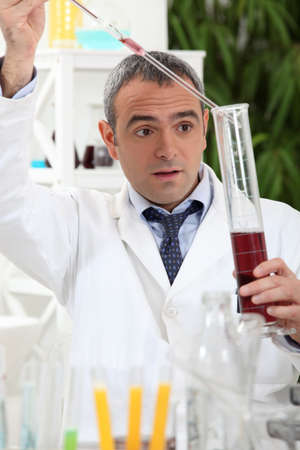 exacting: Man experimenting on red wine Stock Photo