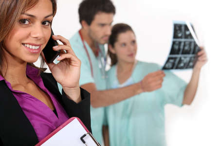 Hospital manager on a phone as medics look at x rays in the background Stock Photo