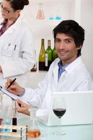 experimenter: Man and woman conducting experiment on wine Stock Photo