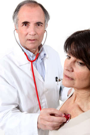 physical test: Doctor listening to a womans chest Stock Photo