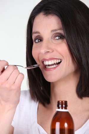 angina: Mujer sonriente tratamiento de la bronquitis con jarabe Foto de archivo