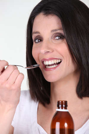 bronchitis: Smiling woman treating her bronchitis with syrup Stock Photo