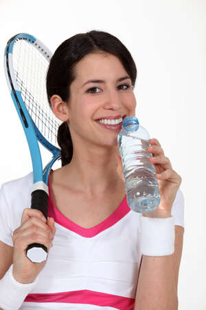 A tenniswoman having a sip of water. photo