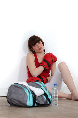 Female boxer sitting on the floor after training photo